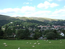 Image shows a small town nestling beneath green hills. In the foreground sheep are grazing.