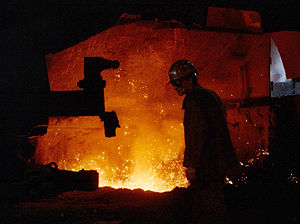 An elderly worker in a helmet is facing his side to the viewer in an industrial hall. The hall is dark but is illuminated yellow glowing splashes of a melted substance.