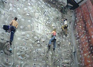 Climbing wall - A indoor rock climbing wall in the UK showing moulded features and coloured route markers.