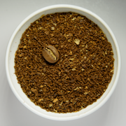 Coarsely grounded coffee beans in white bowl with intact roasted bean.png