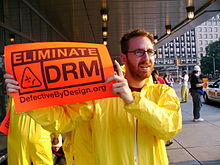 "Man in Tyvek suit holding a ""Eliminate DRM"" sign"