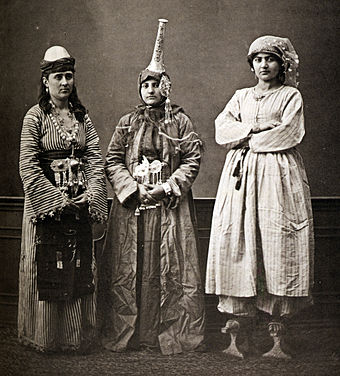 Three Damascene women, 1873: peasant (left), Druze in tantour headdress, and urban lady wearing qabqab shoes Damascusfashion.jpg