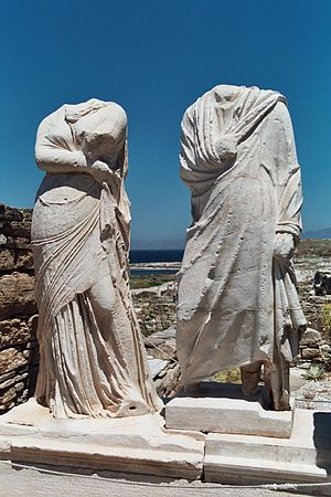 "Clothing in ancient Greece - Statues at the ""House of Cleopatra"" in Delos, Greece. Man and woman wearing the himation"