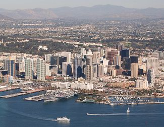 An overhead view of a San Diego's downtown with tall skyscrapers present throughout the area of different colors and sizes. A bay can be seen at the bottom of the image with several boats in the water. In the background are other neighborhoods near the downtown area as well as mountains in the distance.