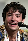 A photograph of Ezra Miller speaking at a convention behind a microphone