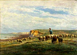 Rural landscape with grassy cliff top to the right, sea and shore in the background to the left. Shepherd in a blue smock stands on cliff top to the right, leaning on his staff, with a flock of sheep grazing around him.