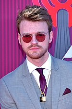 An image of a blonde-haired man wearing a suit and sunglasses against a purple-red backdrop.