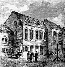 A three-story building with three men standing in front having a conversation, and one or more other people near the building.