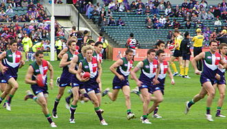 Fremantle Football Club - Left: A commemorative plaque from Victoria Pavilion, Fremantle Oval.. Right: Fremantle players warming up prior to a game in the club's original guernsey, 2009