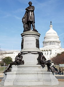 A black statue of Garfield atop an elaborate pillar. The United States Capitol rotunda is visible in the background.