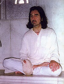 A photo of George Harrison sitting cross-legged with chanting beads in a bag on his right hand