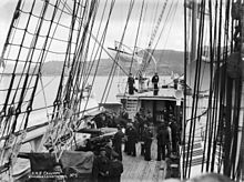 The deck of a sailing ship, viewed from slightly above. Naval cannons protrude through embrasures on this ship's side. About two dozen sailors are on deck. Standing rigging runs from the gunwales to the unseen masts overhead. A raised deck is at the rear, with a boat on davits extended outboard. The ship appears to be in a port, with hills in the background.