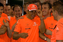 A group of people dressed in orange celebrate, with Hamilton in the middle wearing a baseball cap.