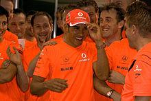 Un groupe de personnes vêtues d'orange célèbre, avec Hamilton au milieu portant une casquette de baseball.