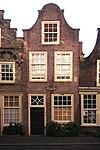 Gepleisterde klokgevel voor huis van parterre, verdieping en zolderverdieping
