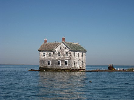 The last remaining house on Holland Island that collapsed and was torn down in the 2010s as erosion and tides reached the foundation. Holland Island house.jpg