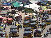 A congested road showing pedestrian traffic, auto-rickshaws and street vendors encroaching on the pavement