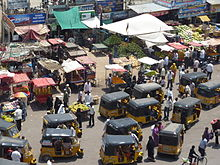 A congested road showing pedestrian traffic, auto rickshaws and street vendors encroaching on the pavement