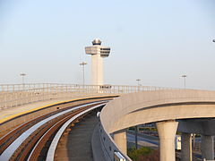 JFK Airport's control tower in the background and an AirTrain guideway in the foreground