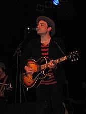 Un homme portant une chemise à rayures rouges et noires, une veste noire, un jean foncé et un chapeau;  il est debout derrière un pied de micro sur une scène et joue de la guitare