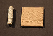 A carved cylindrical object and a small plaque of clay showing a repetitive geometric design