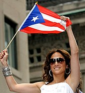 Lopez waving the Puerto Rican flag in 2009 at the Puerto Rican Day Parade in Manhattan.