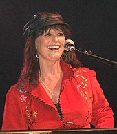 A woman with long brown hair wearing a black cap and a red shirt, sitting at a microphone