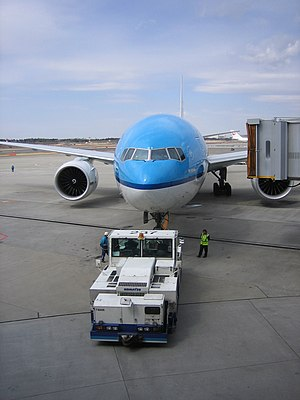 A KLM Boeing 777 being pushed back from a gate...