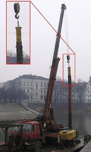 A crane with a pile driver.
