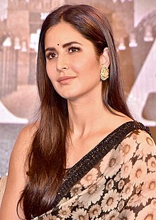 The image features Katrina Kaif in a blue and white sari