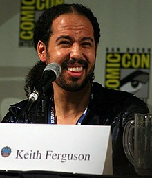 An African-American man gives a wide smile. He sitting in front of a microphone and his eyes are squinted.