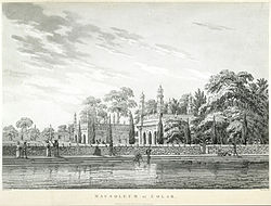 A stone building with onion-domed minarets and a body of water adjoining it. Some men are bathing; others are engaged in conversation. A stone wall separates the water from the building's garden and its leafy trees.