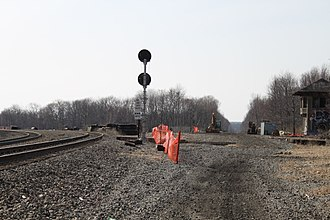 Port Morris Junction - Port Morris Junction on April 9, 2011, looking west-northwest. From left to right: the Montclair-Boonton Line, the track to Port Morris railyard, the signal that controls movements out of the yard, Port Morris Wye (the connection between the Lackawanna Cut-Off and the Port Morris Yard) crossing through the trees about a half-mile (1 km) away, the Cut-Off right-of-way, and Port Morris Tower. The Cut-Off and the Montclair-Boonton Line will be connected behind the photographer.