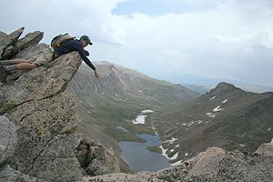 The Sawtooth - A climber leaning on an overhang that's part of the sawtooth. Behind him, to the left, is Mount Evans, and Mount Bierstadt is to the right, off screen. Abyss Lake can be seen below.