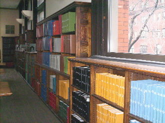 Library binding - Library-bound volumes on wooden bookcases