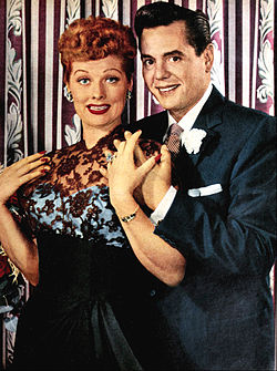 Colored glamourous shot of Lucille Ball and Arnaz standing. Both are smiling to the front. Ball at the left wears a ceremonial gown; Arnaz at right wears a tuxedo.