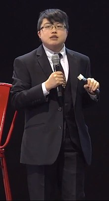 A person in a suit holding a microphone in their left hand with a red chair to their left.