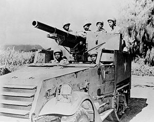 A photograph of a M3 Gun Motor Carriage in a flat area. A mountain is visible in the background, but is obscured by clouds.