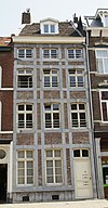 foto van Huis met lijstgevel, met segmentboogvensters in Naamse steen en horizontale en verticale reliefbanden.