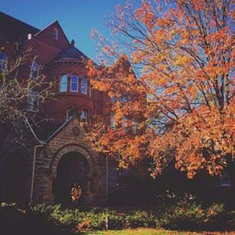 Macalester College - A photograph of the Old Main Building at Macalester College in fall.