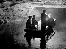 Several people in a jon boat on a river inside a cave.