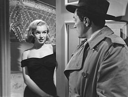 Monroe in The Asphalt Jungle. She is wearing a black dress and stands in a doorway, facing a man wearing a trench coat and a fedora