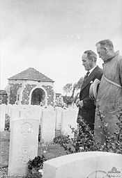 Photograph of two men in suits standing over to the left gazing at a grave marker. Several other graves and a structure are in the background.