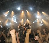 Image shows a band onstage with fans visible in the front of the picture. Some fans are raising their fists and others are raising their hands with the index finger and pinky extended.