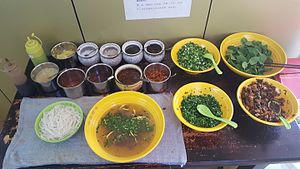 Mixian (noodle) - A large serving of beef mixian noodles with available condiments, as served in a typical local restaurant in Kunming. The broth includes chrysanthemum flowers.