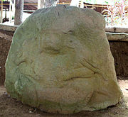 An eroded sculpture carved in relief onto a boulder. It shows a human figure from the front, squatting with the legs splayed. Its elbows are doubled and under each arm it grips a barely distinguishable animal. The figure's face is mostly eroded away but hollows for the eyes and mouth are still visible. The figure wears large ear-spools and a prominent headdress.