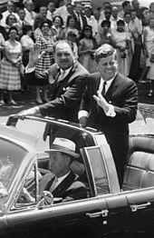"""(L-R) la angla: Aŭtokavalkado por prezidanto Mohammad Ayub Ĥano de Pakistano. En malferma aŭto (Lincoln-Mercury Continental kun vezikpinto): Spionservagento William Greer (veturado); Military Aide al la Prezidanto General Chester V. Clifton (antaŭa seĝo, centro); Secret Service Agent Gerald """"germano"""" Behn (antaŭa seĝo, dekstra; parte kaŝe); Prezidanto Mohammad Ayub Khan (staranta); Prezidanto John F. Kennedy (staranta). Homamaso rigardante. 14-a Strato, Washington, D.C."""