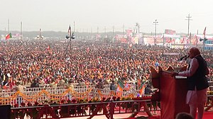 Modi addressing a large crowd from a podium