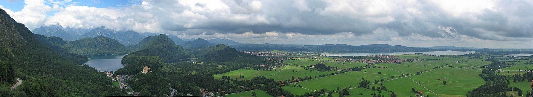 Современная панорама из Нойшванштайна (1,008 m or 3,307 ft[3]), показывающая (слева направо): дорога доступа к дворцу; Альпзее с местностью Хоэншвангау впереди; Замок Хоэншвангау XIX века на холме с Шванзее за ним справа (запад); Местность Альтершрофен с городом Фюссен за ним; Ядро Швангау перед большим водохранилищем Форггензе (1952); Банвальдзее (север)