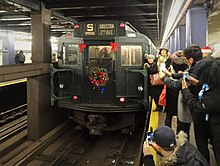 "The Nostalgia Train is seen at Second Avenue station. The train is a dull green. A flower wreath can be seen at the back of the train. Four red lights visible at the back of the train provide slight illumination. On the top of the back of the train the words ""S SPECIAL HOUSTON 2ND AVENUE"" are visible. Several people can be seen taking photos of the train."